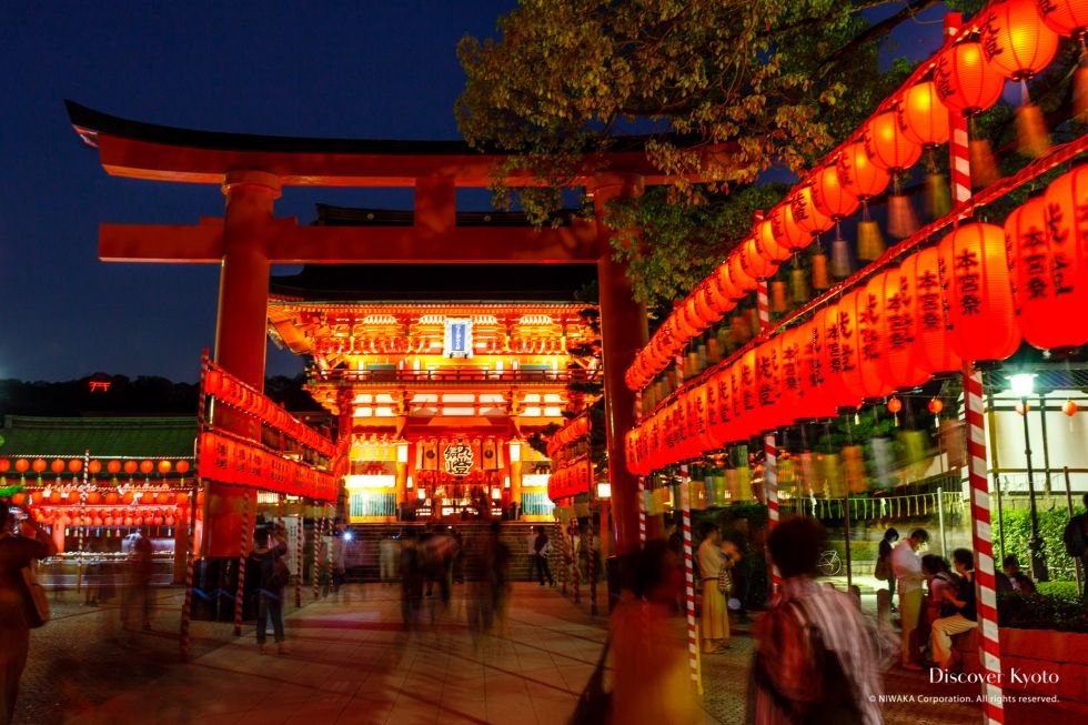 Lanterns and a torii gate at night during the Motomiya-sai festival at Fushimi Inari shrine.
