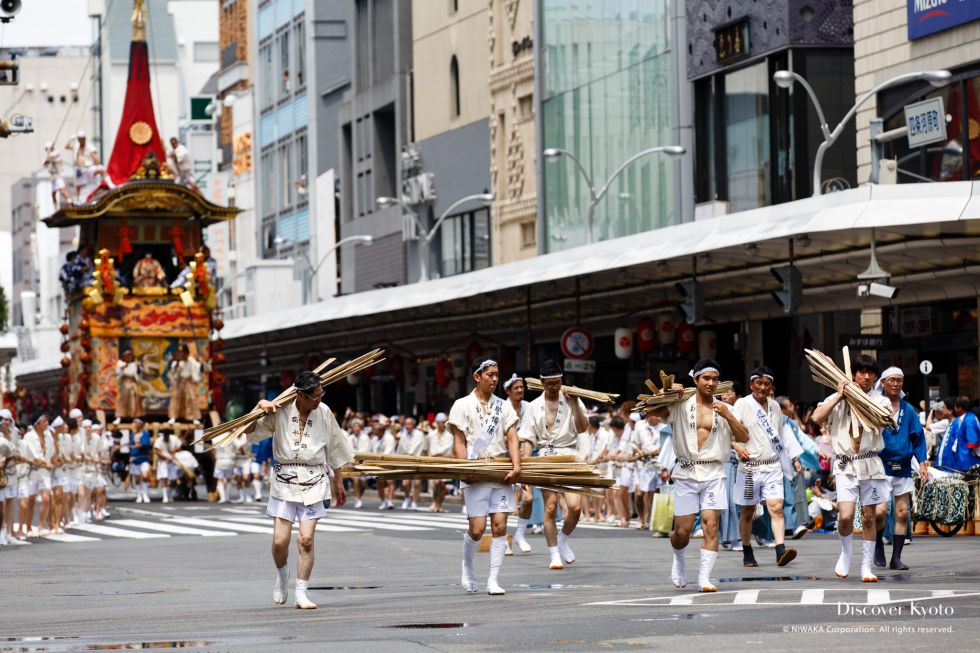 Men carrying bamboo slats ahead of a float during the Yamaboko Junkō parade of the Gion Matsuri.