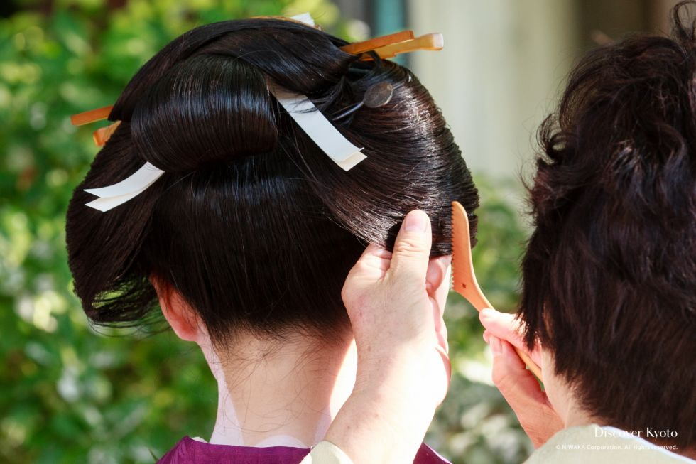 Hot wax is applied to styled hair at the Kushi Matsuri at Yasui Konpiragū.