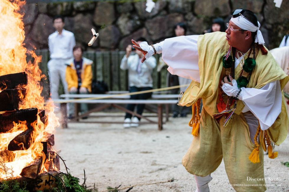A priest throws prayer sticks into a bonfire during the Aki Matsuri at Tanukidani-san Fudō-in.