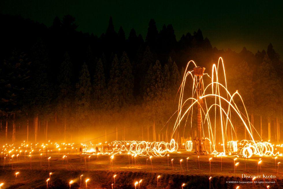 Torches flying towards a basket of tinder at the Hanase Matsu-age.