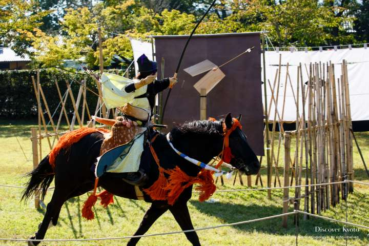 A rider aims for a large wooden target during the Kasagake Shinji at Kamigamo Shrine.