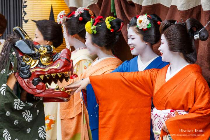 Geiko and maiko hold out their hands during the Zuiki Matsuri at Kitano Tenmangū.