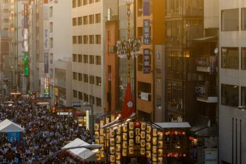 Crowd and float at sunset during the Yoiyama nights of Gion Matsuri.