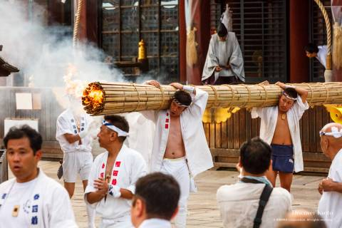 Men carry a lit torch during the Omukae Chōchin ritual at Yasaka shrine.