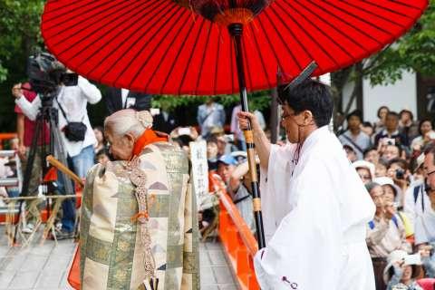 A priest accompanied by a red umbrella at Takekiri-eshiki at Kurama-dera.