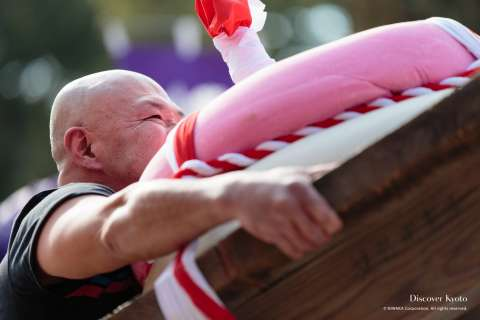 Competitor lifting the rice cake at the Mochi-age at Daigo-ji temple.