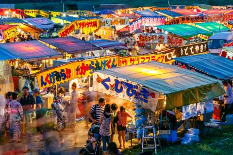 The glow of the food stalls takes over as it gets dark at Hozugawa Fireworks in Kameoka