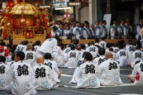 Men sit and wait before the omikoshi portable shrine during the Mikoshi Procession of Gion Matsuri.