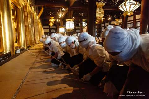 Masked cleaners beating the floor during the Osusuharai at Nishi Hongan-ji.