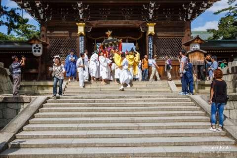 The portable shrine procession departs the shrine during the Zuiki Matsuri at Kitano Tenmangū.