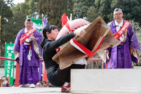 Monks and person lifting rice cake at the Mochi-age at Daigo-ji temple.