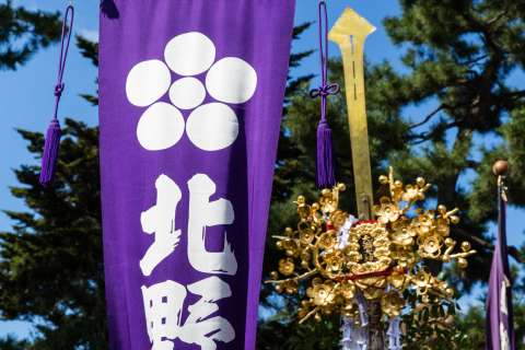 Sacred halberds and a banner held high at the Zuiki Matsuri at Kitano Tenmangū.