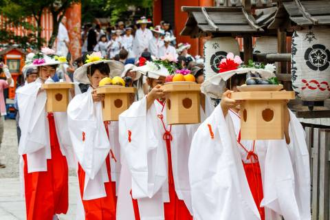 Priestesses carry offerings during the Hanagasa Junkō at Yasaka shrine.