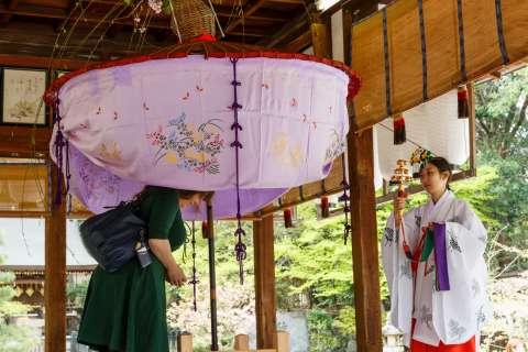 Blessings from a shrine priestess during Yasurai Matsuri at Imamiya Shrine.